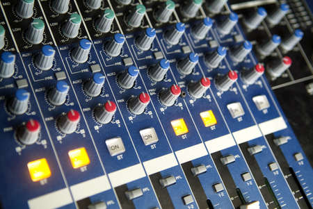 bottons: An array of rotary controls, sliders, and bottons on audio mixing console.