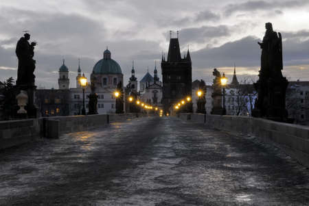 Prague, Charles Bridge, built in 12th century, with lights on early morning, Old Town in counterlight. Stock Photo - 8683106