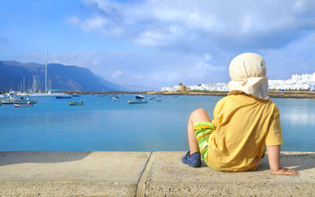 Two year old boy in yellow shirt and a sun hat watching harbor area in Caleta de Sebo, main harbor in Graciosa Island; island of Lanzarote over Rio channel on a backdrop; Graciosa, Canary islands, Spain Stock Photo - 8762577