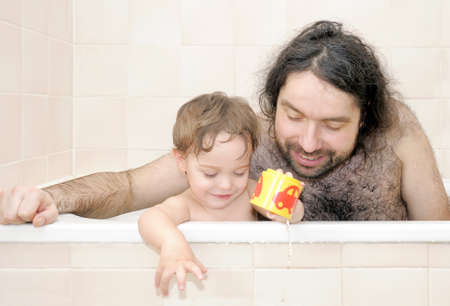 Father bathing together with his half-year-old baby-boy photo