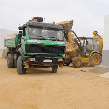 Front end loader loading a truck on a shore of Graciosa; Canary islands, Spain photo