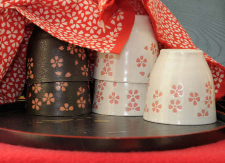 dera: Japanese porcelane cups under red cotton cloth with matching floral design. The cups are beautifully glazed. The shot was made in one of the small stalls offering tea by Kiomizu Dera temple in Kyoto, famous for its tasty water.