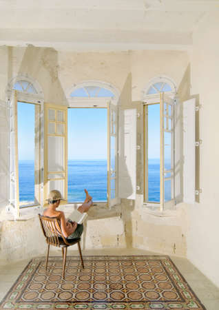 Young pregnant woman reading a book by the window facing the sea. Malta photo