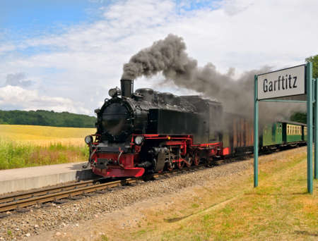 Steam train approaching station of Garftitz on island Rugen, Northern Germany