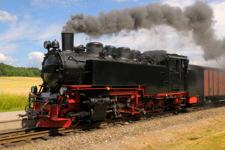 railway station: Steam train with black smoke running on island Rugen, Northern Germany