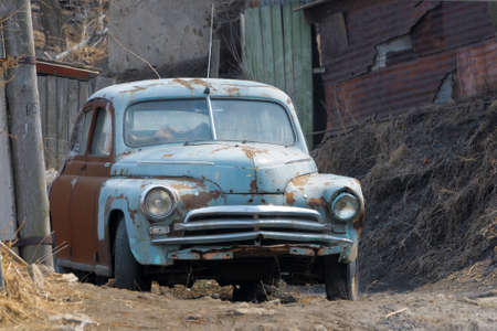 rusty car: Old rusty car next to a poor house. Vladivostok, Russia