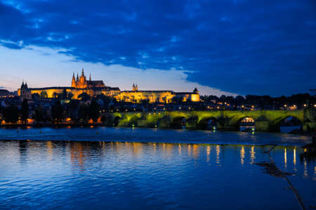 Evening view of Prague Castle and Charles Bridge over Vltava river from Novotneho Lavka, Prague, Czech. The illumination on the bridge has been switched on a few seconds ago, hence the greenish hue of lamps that are warming up photo