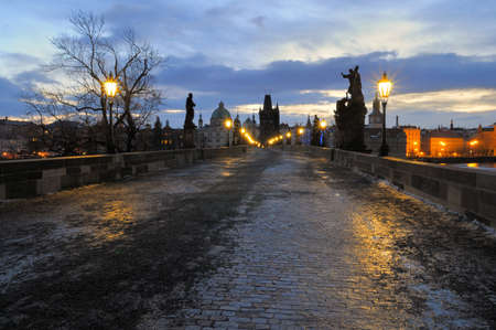 Prague, Charles Bridge with lights on early morning, Old Town in counterlight. Stock Photo - 9171967
