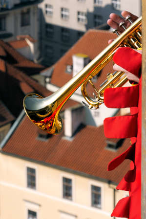 tight focus: Every hour a musician in period clothes climbs the Tower of the Old Town Hall to play a trumpet from the top. Tight shot from the corner erker, only the trumpet and part of the red sleeve are visible.  Focus on the instrument.