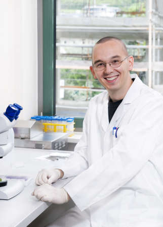 Young scientist in while lab coat  smiles at the camera Stock Photo - 9993529