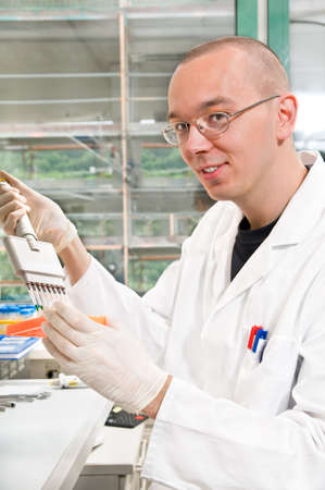 Young scientist in while lab coat  smiles at the camera Stock Photo - 9990976