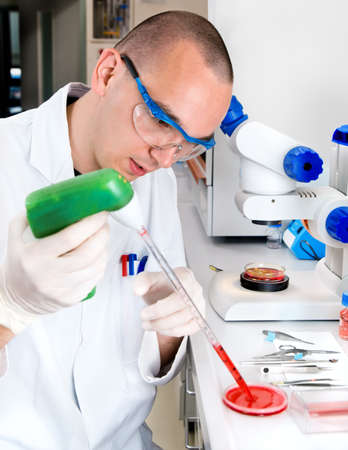 biologist: Young scientist in while lab coat works in the lab