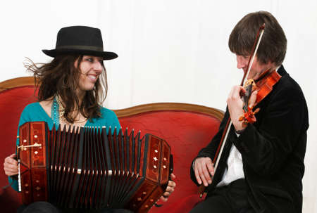 bandoneon: Argentine tango musicians with bandoneon and violin on a red sofa Stock Photo