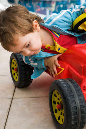 Little boy examines wheels of his bobby-car Stock Photo - 10521684