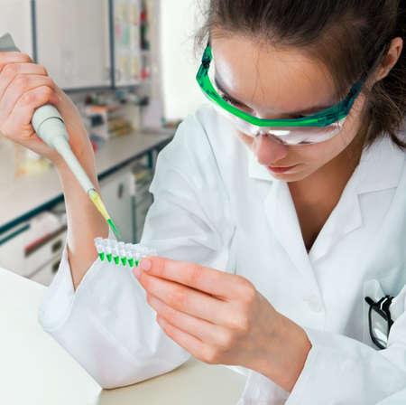 Nowoczesnym laboratorium; młodych naukowców w białym Herb ładuje próbek pcr