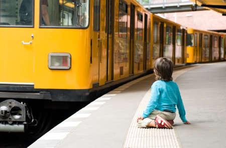 u bahn: Three year old boy watches yellow train sitting on a safety line along tube platform; Berlin, Germany Stock Photo
