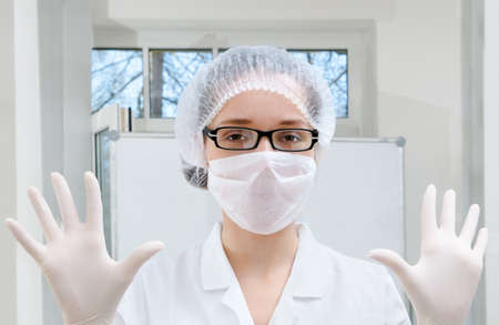 Lab worker in white coat demonstrates protective wear photo