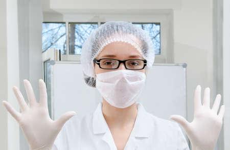 enfermera con cofia: Trabajador de laboratorio en bata blanca demuestra el desgaste de protecci�n