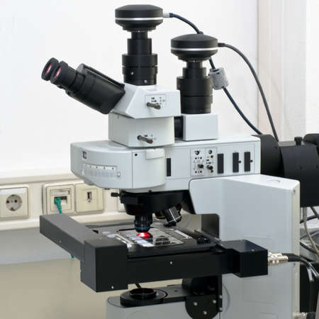 sofisticated: Modern high throuput fluorescent microscope scanning several biopsy samples Stock Photo
