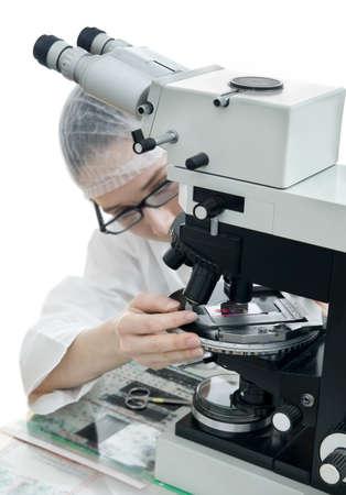 Pathologist tunes her microscope; isolated on white background Stock Photo - 11724047
