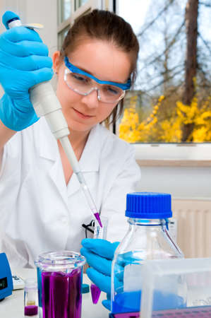 loads: Young female scientist loads histological dye into plastic tube