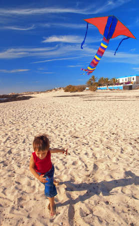 Little boy on a beach runs with a kite photo