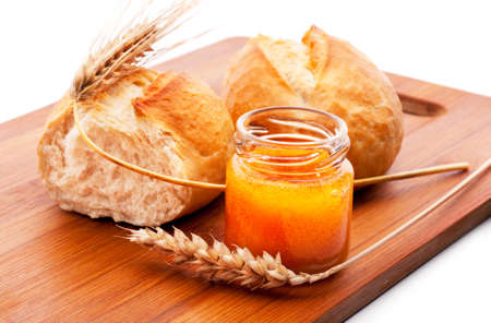 Freshly baked bread rolls, wheat ears and honey