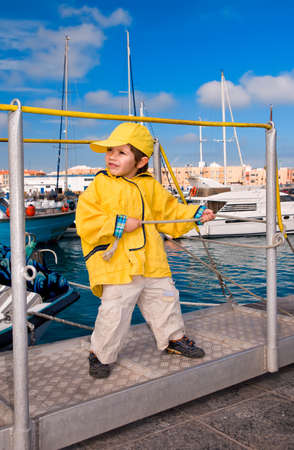 marina water: Little boy in yellow windbreaker pulls ropes at marina pier