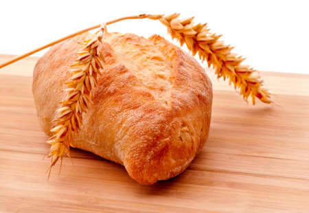 A half-sized ciabatta roll and wheat ears on cutting board, isolated on white photo