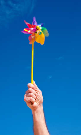 Hand holds rotating toy windmill over blue sky, copy space, slow shutter speed to catch motion photo
