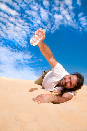 Thirsty man in the desert with a bottle of water photo
