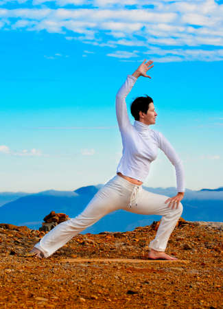 Young woman practicing yoga in front of a mountain Stock Photo - 12353712