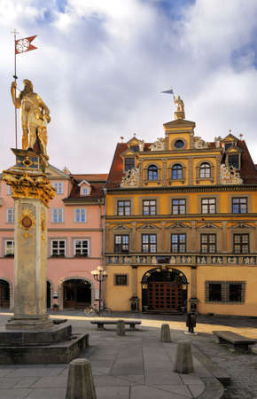 popularly: Red Ox House (Haus zum Roten Ochsen), a historical building on Fish Market Square in Erfurt nou housing an art gallery; the golden statue on the left is popularly known as Roland.  Stock Photo