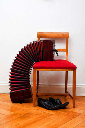 bandoneon: streched Bandoneon on a red chair with Tango shoes beneath