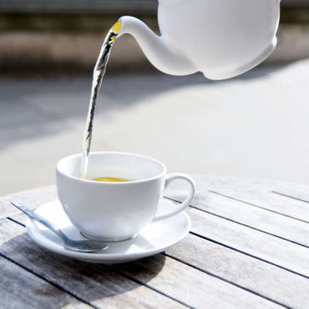 english tea: Pouring green tea from white ceramic teapot into a matching tea cup