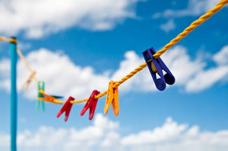 Colorful clothes pegs on a yellow rope against blue sky with clouds