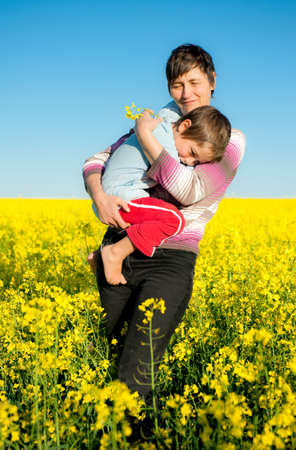 Mother carried her child through rapeseed field photo