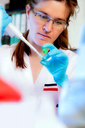 investigador cientifico: Retrato de un cient�fico con un dispensador autom�tico de l�quidos en el moderno laboratorio, someras DOF Foto de archivo