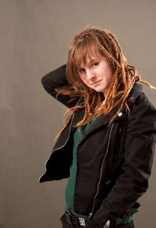 dreadlocks: Cheeky niña con dreadlocks en un fondo marrón