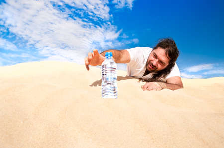 extreme angle: Thirsty man in the desert reaches for a bottle of water Stock Photo