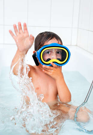 Little boy in a diving mask splashes in a bath photo