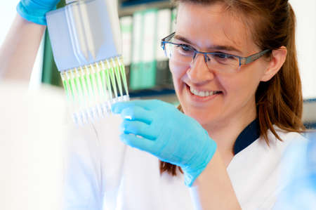 Smiling scientist loads samples with automatic multichannel pipette Stock Photo - 14347235