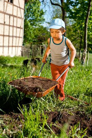 Little farmer moves a heavy wheelbarrow full of earth photo