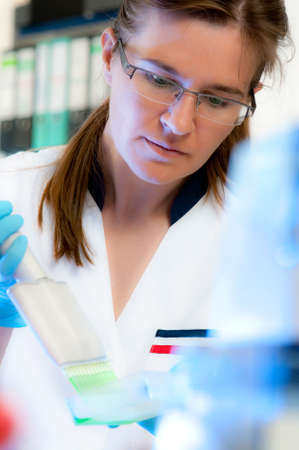 Scientist works with multichannel pipette photo