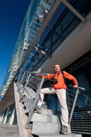 Traveller with photo camera on the stairs of a modern building Stock Photo - 14533313