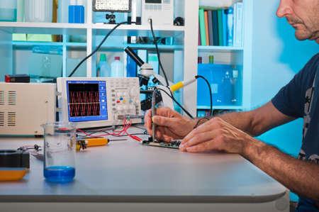 circuitos electronicos: Un sonidista pone a prueba los componentes electr�nicos con un osciloscopio en el centro de servicio Foto de archivo