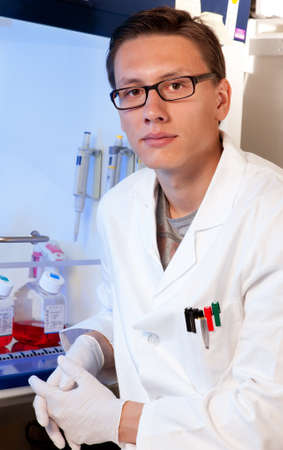 Young scientist sits next to cell culture hood, half body, focus on the eyes Stock Photo - 14695195