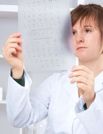 Young female medtech checks results of caryotype test