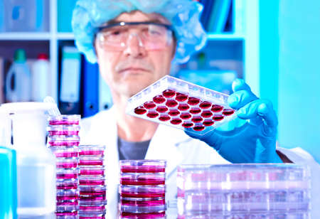 research worker: Senior tech works with cultured cells in modern lab Stock Photo