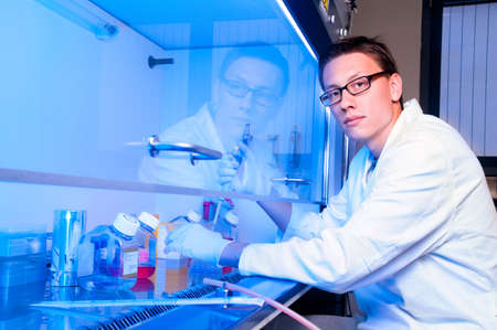 Young tech works with cell cultures under sterile hood